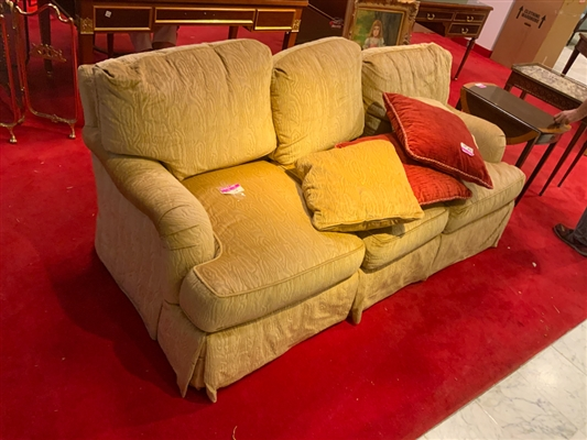 Tan sofa with two upholstered pillows